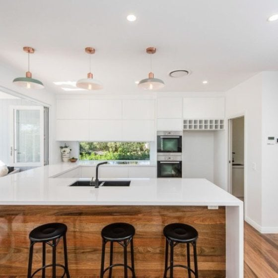 kitchen with timber flooring and white benchtops and pendent lighting